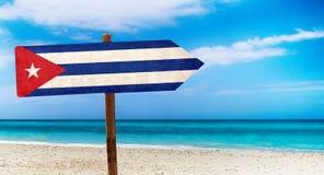 De vlag van Cuba op houten lijstteken op strandachtergrond Het is de zomerteken van Cuba stock afbeelding