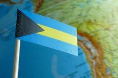 De vlag van de Bahamas met een bolkaart als achtergrond Royalty-vrije Stock Foto's