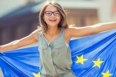 De vlag van de EU Leuk gelukkig meisje met de vlag van de Europese Unie Jonge tiener die met de Europese Unie vlag in de stad gol royalty-vrije stock afbeeldingen