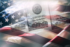 De vlag van de V.S. en Amerikaanse dollars Amerikaanse vlag die in de wind en 100 dollarsbankbiljetten blazen op de achtergrond Stock Afbeeldingen