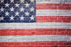 De vlag van de V.S. op bakstenen muur wordt geschilderd die vierde van de Achtergrond van Juli stock fotografie