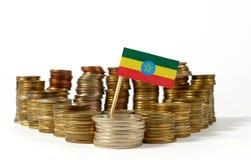 De vlag van Ethiopië met stapel geldmuntstukken Stock Foto