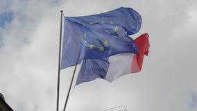 De vlag van Frankrijk en de Europese Unie golven in de wind Tegen de achtergrond van een bewolkte hemel Langzame Motie stock footage