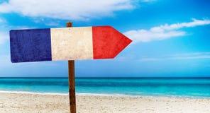De vlag van Frankrijk op houten lijstteken op strandachtergrond Het is de zomerteken van Frankrijk royalty-vrije stock fotografie