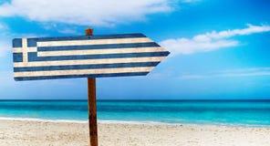 De vlag van Griekenland op houten lijstteken op strandachtergrond Het is de zomerteken van Griekenland royalty-vrije stock fotografie