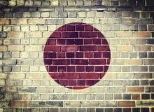 De vlag van Grungejapan op een bakstenen muur Stock Foto's