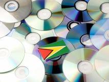 De vlag van Guyana bovenop CD en DVD-stapel op wit wordt geïsoleerd dat Stock Foto's