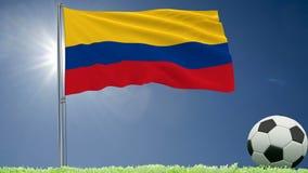 De vlag van het fladderen van Colombia en een voetbal rolt op het gazon, het 3d teruggeven Stock Foto's
