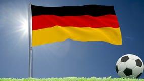 De vlag van het fladderen van Duitsland en een voetbal rolt op het gazon, het 3d teruggeven Royalty-vrije Stock Afbeeldingen