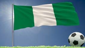 De vlag van het fladderen van Nigeria en een voetbal rolt op het gazon, het 3d teruggeven Stock Foto's