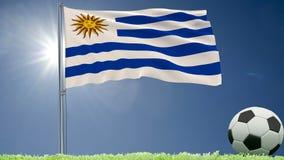 De vlag van het fladderen van Uruguay en een voetbal rolt op het gazon, het 3d teruggeven Stock Afbeeldingen