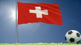De vlag van het fladderen van Zwitserland en een voetbal rolt op het gazon, het 3d teruggeven Royalty-vrije Stock Foto's