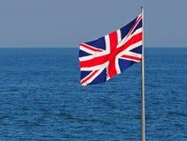 De vlag van het Verenigd Koninkrijk tussen het overzees en de hemel royalty-vrije stock foto