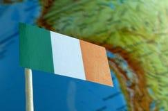 De vlag van Ierland met een bolkaart als achtergrond royalty-vrije stock foto's