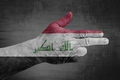 De vlag van Irak op mannelijke hand zoals een kanon wordt geschilderd dat royalty-vrije stock foto