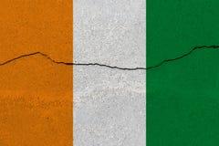De vlag van Ivoorkust - van Ivoorkust op concrete muur met barst stock afbeeldingen