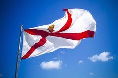De vlag van Jersey van kanaaleilanden tegen blauwe hemel Royalty-vrije Stock Foto