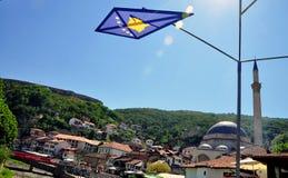 De vlag van Kosovo met een mooie mening van het oude deel van Prizren stock foto's