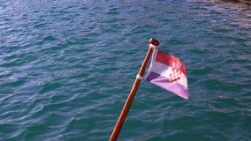 De vlag van Kroatië vast op de boot die in de wind golven stock videobeelden