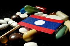 De vlag van Laos met partij van medische die pillen op zwarte achtergrond wordt geïsoleerd Stock Foto's