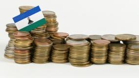 De vlag van Lesotho met stapel geldmuntstukken stock footage