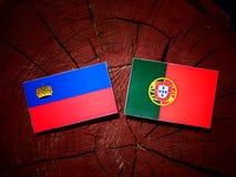 De vlag van Liechtenstein met Portugese vlag op een geïsoleerde boomstomp stock afbeelding