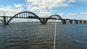 De vlag van de metaaloekraïne op jachtachtergrond van rivier Dnieper en brug over rivier stock footage