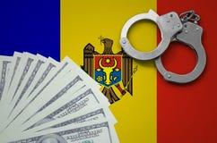 De vlag van Moldavië met handcuffs en een bundel van dollars Het concept onwettige bankoperaties in de munt van de V.S. royalty-vrije stock foto