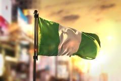 De Vlag van Nigeria tegen Stad Vage Achtergrond bij Zonsopgang Backligh Stock Fotografie