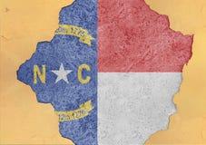 De vlag van Noord-Carolina van de staat van de V.S. schilderde op concreet gat en barstte muur royalty-vrije stock afbeeldingen