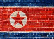 De vlag van Noord-Korea op een bakstenen muur Stock Foto's