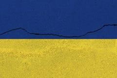 De vlag van de Oekraïne op concrete muur met barst stock afbeelding