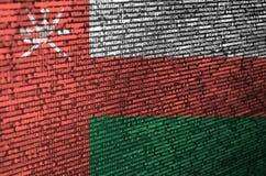 De vlag van Oman wordt afgeschilderd op het scherm met de programmacode Het concept moderne technologie en plaatsontwikkeling royalty-vrije stock fotografie