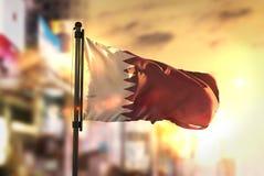 De Vlag van Qatar tegen Stad Vage Achtergrond bij Zonsopgang Backlight Royalty-vrije Stock Afbeeldingen