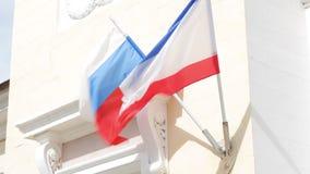 De vlag van Rusland en de vlag van de Republiek die de Krim in de wind fladderen stock video