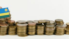 De vlag van Rwanda met stapel geldmuntstukken stock videobeelden