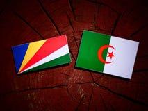 De vlag van Seychellen met Algerijnse vlag op een geïsoleerde boomstomp stock illustratie