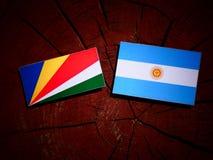 De vlag van Seychellen met Argentijnse vlag op een geïsoleerde boomstomp vector illustratie