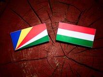 De vlag van Seychellen met Hongaarse vlag op een geïsoleerde boomstomp stock illustratie