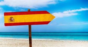 De vlag van Spanje op houten lijstteken op strandachtergrond Het is de zomerteken van Spanje royalty-vrije stock fotografie