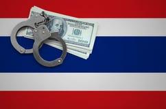 De vlag van Thailand met handcuffs en een bundel van dollars Het concept het breken van wet en de dievenmisdaden stock foto