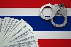 De vlag van Thailand met handcuffs en een bundel van dollars Het concept onwettige bankoperaties in de munt van de V.S. stock foto
