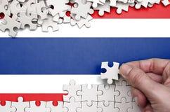 De vlag van Thailand wordt afgeschilderd op een lijst waarop de menselijke hand een raadsel van witte kleur vouwt stock foto's