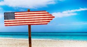 De vlag van de V.S. op houten lijstteken op strandachtergrond Het is de zomerteken van de V.S. royalty-vrije stock fotografie