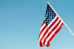 De vlag van Verenigde Staten blaast in de wind tegen een blauwe hemel in bijlage aan de muur van de kant Royalty-vrije Stock Fotografie