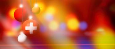 De vlag van Zwitserland op Kerstmisbal met vage en abstracte achtergrond Stock Foto