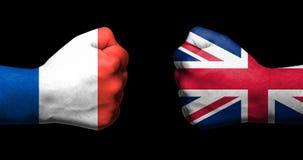 De vlaggen van Frankrijk en het Verenigd Koninkrijk schilderden op twee dichtgeklemde vuisten die elkaar op zwart achtergrond/het stock fotografie