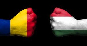 De vlaggen van Roemenië en Hongarije schilderden op twee dichtgeklemde vuisten die elkaar op zwart achtergrond/Roemenië-Hongarije royalty-vrije stock afbeelding