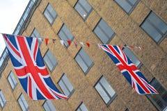 De vlaggen van Union Jack hangen over straat Royalty-vrije Stock Foto's
