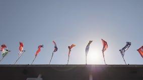 De vlaggen van de wereld hangen over het gebouw stock videobeelden